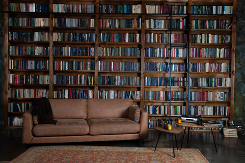 an inviting brown leather sofa welcomes you to nestle among a roomful of books organized on floor to ceiling dark wood bookcases.