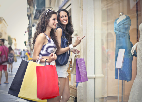 two attractive young women dressed in shorts and t-shirts window shop holding colorful purchases